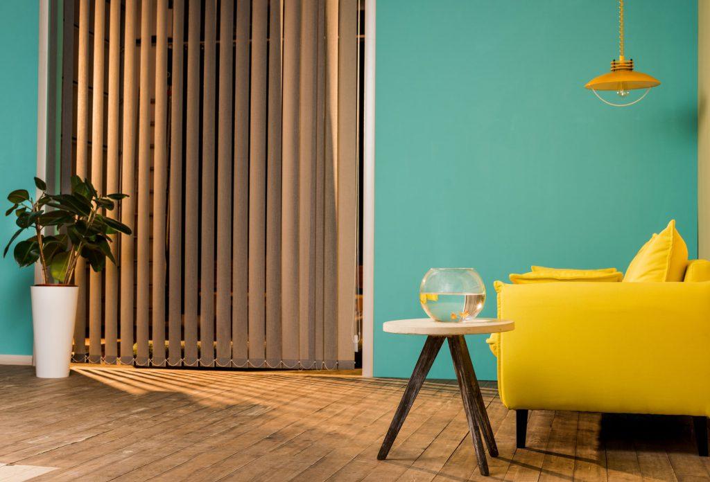 gelbes Sofa vor grüner Wand
