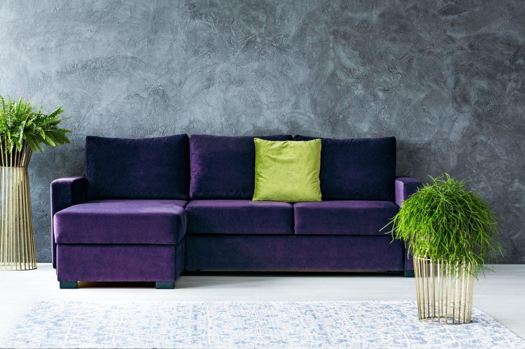 lila Sofa mit grünem Kissen