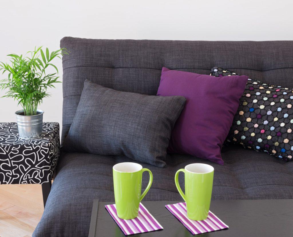 grüne Tassen vor graumem Sofa mit lila Kissen