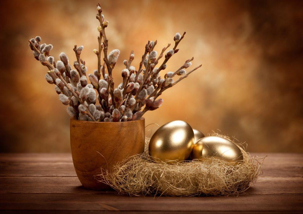 Weidenzweige und Eier in goldenen Osterfarben