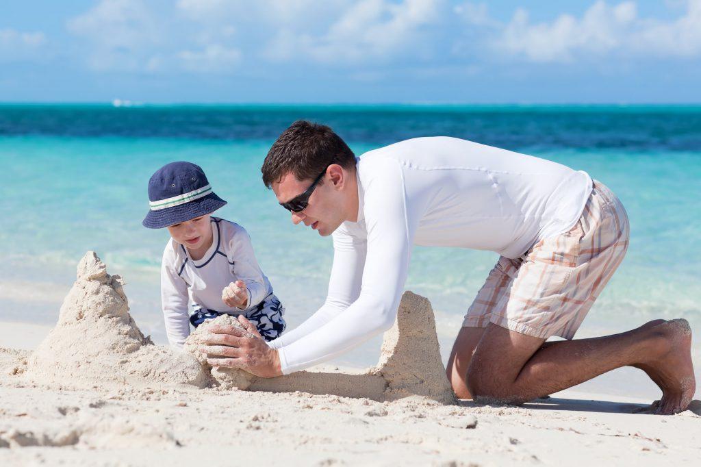 Mann und Kind am Strand statt Herrentag zuhause